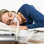 Image of a woman with sleep apnea machine