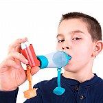 Image of a boy taking an inhaler