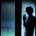 Silhouette of a man standing behind frosted glass holding up one hand while blue light shines behind him.