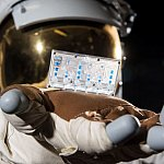 A NASA spacesuit is shown with a kidney tissue chip in hand.