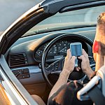 Boy using cell phone with two hands behind the driver's wheel