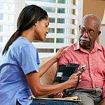 A nurse wraps a blood pressure cuff around a man's arm.