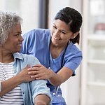 Caring nurse smiles at an African American senior female patient.