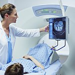 Female doctor showing CT scan to patient in examination room at hospital
