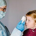 Medical professional checks girl's body temperature.