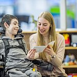 A boy in a wheelchair is indoors in his classroom. He is being assisted by his classroom helper. She is reading a story to him.