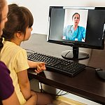 Mother with her daughter video calling doctor from home - stock photo