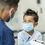 Young boy wearing a mask at a doctors appointment - stock photo
