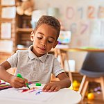 Beautiful african american toddler drawing using paper and marker pen at kindergarten - stock photo