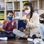 Preschool teacher, students in class, wearing masks - stock photo