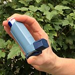 Photo of a person's hand holding an asthma inhaler.