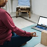 A woman doing yoga infront of TV