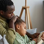 Father reading with young daughter.
