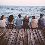 Young multi-ethnic hipster friends and couples sitting on wooden jetty - stock photo