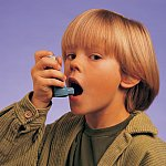 A young boy using an inhaler