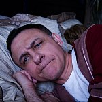 Photo of an angry man lying awake in bed - cropped