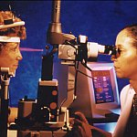 Photo of a female doctor performing laser eye therapy on a female patient