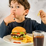 Photo of little boy eating fast food
