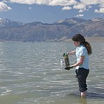 Photo of a woman standing in shallow water with a specimen jar