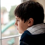 Photo of a young boy looking out a window cropped