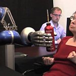 A woman controlling a robotic arm to grasp a bottle.