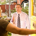 An untrustworthy man in a senior's doorway.