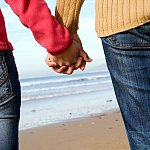 Couple holding hands on beach in winter