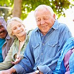 Group of older adults socializing outdoors.