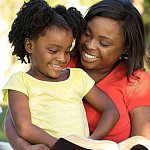 African-American mother and daughter reading outdoors.
