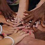 Diverse people stacking their hands together
