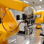 A robot arm (foreground) retrieves assay plates from incubators to place them at compound transfer stations or hand them off to another arm (background).
