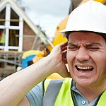 Construction worker holding ears on building site