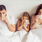 Family in bed together with colds