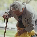 Grandfather with a cane hugged by a child
