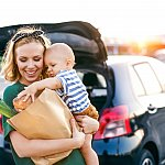 Young mother with baby boy carrying groceries to car