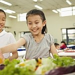 Students reaching for healthy food in school cafeteria.