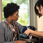 Health care worker setting up to take a woman's blood pressure.