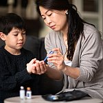 Mother helping son check blood sugar level