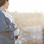 Pregnant woman overlooking a city