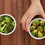 A woman's hand holding a bowl of brussel sprouts, with a bowl of cooked broccoli to the left.