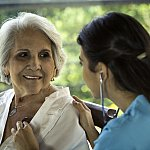 Physician listens to senior patient's heart