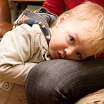 Young boy hiding between a parent's knees