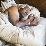 Senior African American man asleep in bed