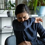 Young woman coughing into her elbow