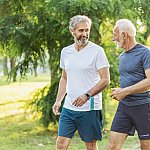 Two senior men walking and talking in the park