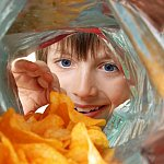 View from inside a potato chip bag of a boy enthusiastically looking in
