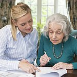 Woman helping senior with paperwork
