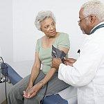 Doctor measuring blood pressure of senior Black woman