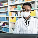 Female pharmacist with face mask at a computer