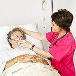 Hospital nurse helping senior woman breath through an oxygen mask